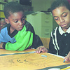 1/15/96--MR King 1--Takaaki Iwabu photo-- Kevin Wilson, 6, left, waches 11-year-old Arus George's art work of Martin R. King at Niagara Community Center Wednesday. The children at the Center are preparing for the poster contest that will be held at Dr. King's memorial lucheon at the Center.