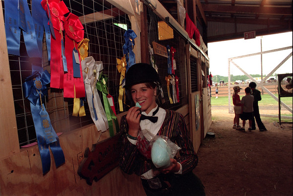 98/07/31--MEDINA/4H FAIR--DN CAPPELLAZZO PHOTO--13-YR-OLD KRISTINA GAYLORD, OF KENDELL, TAKES A BREAK BETWEEN COMPETITIONS TO SNACK ON COTTON CANDY. THE EQUESTRIAN RIDER STANDS UNDER HER MANY RIBBONS FOR ENGLISH WESTERN AND JR. WESTERN RIDING AT THE STABLES AT THE 4H FAIR.<br /> <br /> MEDINA