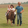 "6/12/97 Cerebral Palsy Center 2 - James Neiss Photo - Little Jodie Hague 3yrs of Youngstown, gets a ride on ""Fred"" the Pony with help from Margret Nawrocki, Physical therapist  and Ken Hill of Hills Stables."
