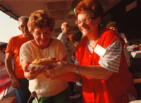 8/1/97 Italian Experience 3--Takaaki Iwabu photo-- Mary Pizzimenti, left, and Norma Ruggiero share a laugh as they cook and serve Italian sausage sub during The Italian Experience at E. Dent Lackey Plaza Saturday. <br /> <br /> grapevine photo