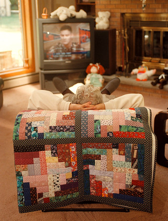97/10/01 Quilters 3 - James Neiss Photo - Dominic Bianca of Grand Island kicks back to watch some sports tv. On his chair back is a Strip Pieced Half Log Cabin Quilt.