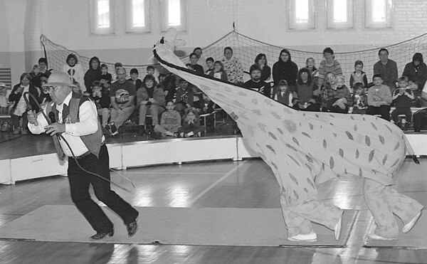 "3/16/97--CIRCUS--DAN CAPPELLAZZO PHOTO--COL. MEL SILVERLAKE, OF THE CARTOON CIRCUS, RUNS FOR COVER FROM  ""JARGO"" THE GIRAFFE AT THE TONAWANDA ARMORY"
