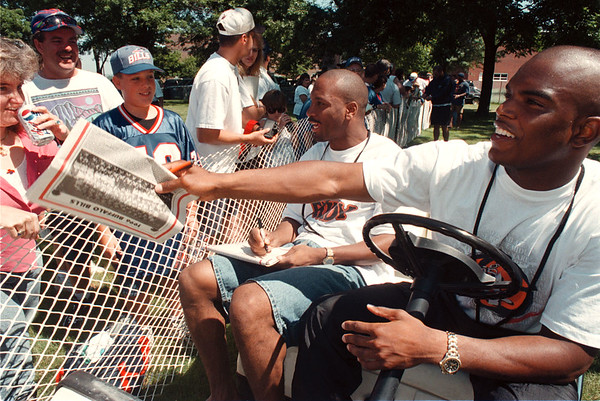 7/11/97- bills camp 2-- Bills Marlon Kerner and Jeff Burris take a time for autograph for the fans as they leave the ground for a lunch break during the training camp.