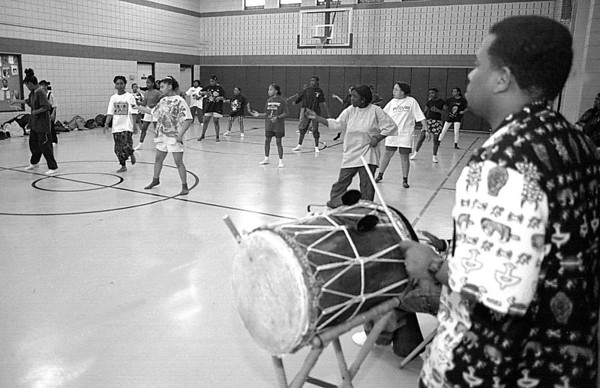 "3/17/97--DANCE DRUMMER--DAN CAPPELLAZZO PHOTO--AFRICAN TRADITONAL ""JU JU"" DRUMMER MARLO WRIGHT, OF BUFFALO, POUNDS OUT A RHYTHM AS LOCAL TEEN DO TRADITONAL DANCES AT THE FAMILY RESOURCE BLDG., 3001 9TH.<br /> <br /> GR"