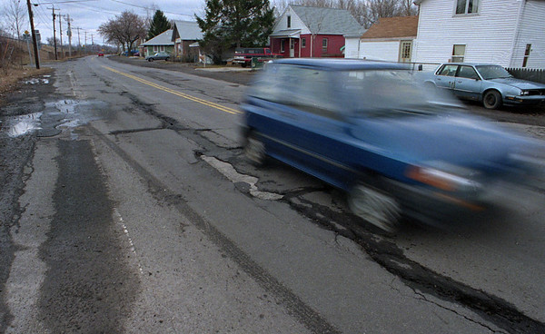 3/2/97--POTHOLES--DAN CAPPELLAZZO PHOTO--A CAR SPEEDS ALONG OVER A PATCH OF POTHOLES ON BUFFALO AVE.<br /> <br /> NEWS/LOCAL