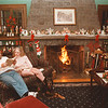 98/12/03 Cameo Inn 1 - Vino Wong Photo - Owners of Cameo Inns Greg and Carolyn Fisher sit back and relax with the unplugged version of life in the library room of their home, 3881 Lower River Road, Youngstown.