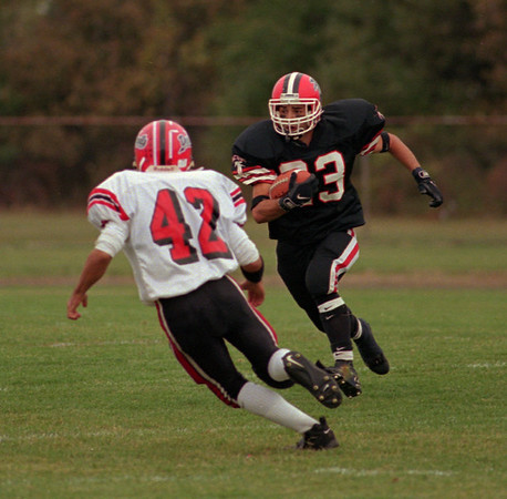 98/10/03  N-W Football *Dennis Stierer Photo -<br /> Niagara-Wheatfield Falcons #23, Nick Condino does some fancy footwork to dodge John D'Andrea of Clarence.