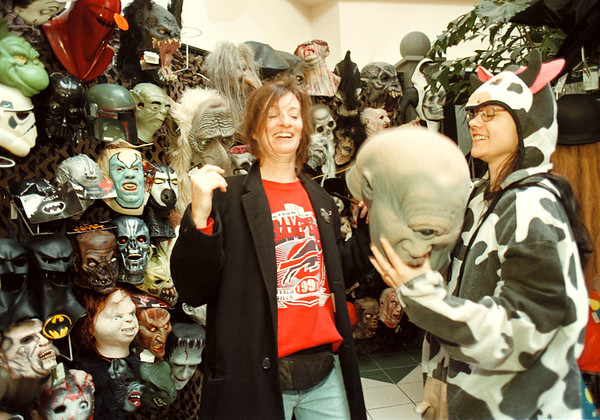 10/16/97-- halloween 1--Takaaki Iwabu photo-- Melissa Papiernik, right, manager of Spencer Gifts Halloween Head Quarters, shows one of masks the store features to Charmaine Crowley of Lewiston. Head Quarter is located in Summit Park Mall. <br /> <br /> feature, Sunday, color