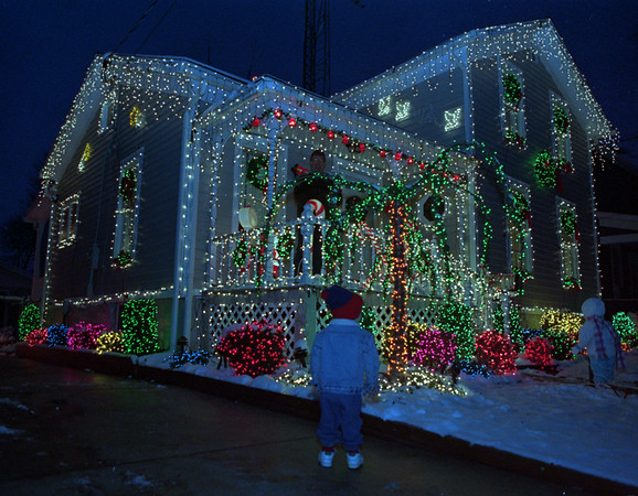 """97/12/12--HOLIDAY HOUSE--DAN CAPPELLAZZO PHOTO--54 WALNUT ST HOMEOWNER PAUL CREGO LOOKS OUT FROM THE  PORCH OF HIS HOME TO SAY HIGH TO 2-YR-OLD TRACY MARACLE WHO IS TAKEN BY THE 28,000 XMAS LIGHTS ON CREGO'S HOME.<br /> <br /> SATURDAY 38P6 X  5"""""""
