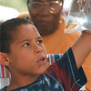 97/08/08 Family Festival 2 - James Neiss Photo - Anthony McTere 9yrs of Falls street checks out a fish his cousin won at the African-American Family Festival.