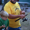 98/08/06 Scout Anglers2-Rachel naber Photo-Eric Mitchell from Den #3 watches pack leader Kevin Johnson demonstrate the differences between fishing poles used for the sport.