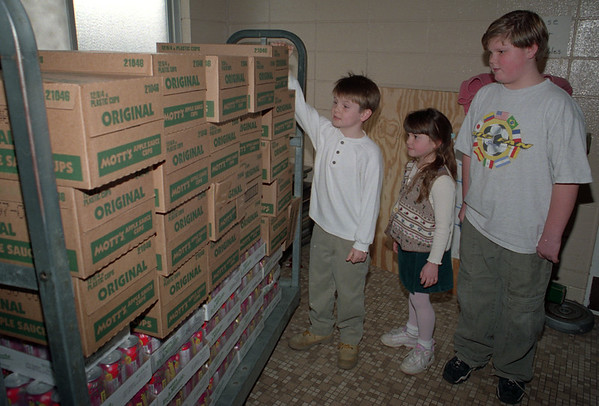 98/12/07 salvation/apple sauce--(ltor) 7-yrold ethan randall, his sister 5-yr-old caroline and james mulrain, 11, all of lkpt, check out the mountain of apple sauce they donated to the salvation army.