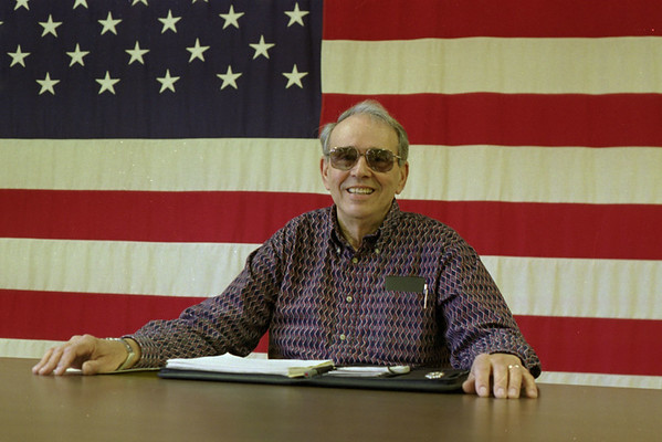 98/04/10 Lyndonville Mayor *Dennis Stierer - Marc Scarr, the new mayor of Lyndonville sits in the local meeting room in front of a huge American Flag.