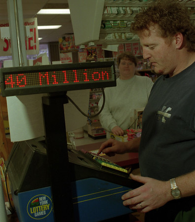 98/02/20 - 40 Mil Lotto *Dennis Stierer photo - Nick Rubert prints out another hopeful winning ticket at Kenyon's, downtown, for Kelly Hall. The jackpot is now 40 million.