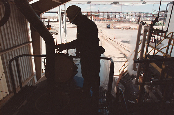 4/10/97--CAUSTIC/OLIN CHEMICAL 2--DAN CAPPELLAZZO PHOTO--CAUSTIC OPERATOR CARL BLOSS CHECKS THE HATCH ON A TRAIN CAR IN THE LOADING GARAGE.<br /> <br /> NEWS/1A