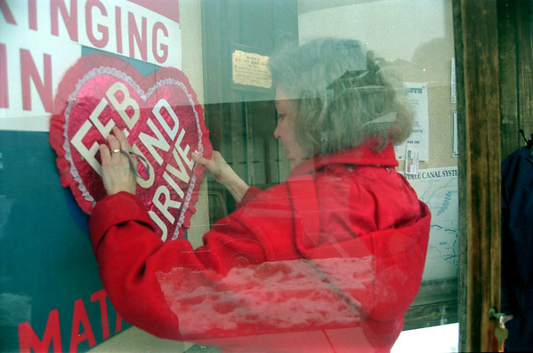 98/1/27 Middleport Tourists?-Rachel Naber Photo-Janet Lyndaker hangs a heart on the Middleport community bulletin board to advertise the 10th anniversary of the tourism and beautification commitee.