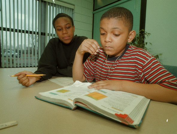 98/03/04 Living Large - James Neiss Photo - L-R - Bionca Allen 17yrs/10th grade, tutors Javon Presley 9yrs/3rd grade, as part of the Living Large Tutorial Program at the Niagara Falls Housing Authority Family Resource Center. It's an after school program for students kg-12th and has a certified teacher on hand. Call Yolanda Walker, resource assistant at 285-5374 for more info.