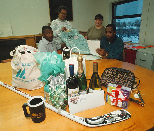 1/30/97 Center Auction - James Neiss Photo - Niagara Community Center Association, Inc. 69th Annuyal Meeting & Banquet Dinner Silent Auction Items. L-R are Renwick Feagin, Recording & Coirisponding Secritary/Programs Assistant, Marilyn Lyman, Amdassidor, Catherine DeSantis, Interm Exec. Director and Tony Newsome, Recreation Director.
