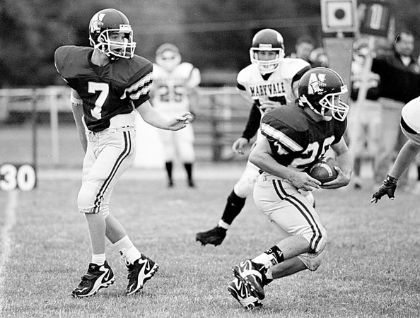 98/10/03 Newfane Football  #2  *Dennis Stierer Photo -<br /> Newfane's quarterback #7 turns to make sure his handoff went smooth to #26.