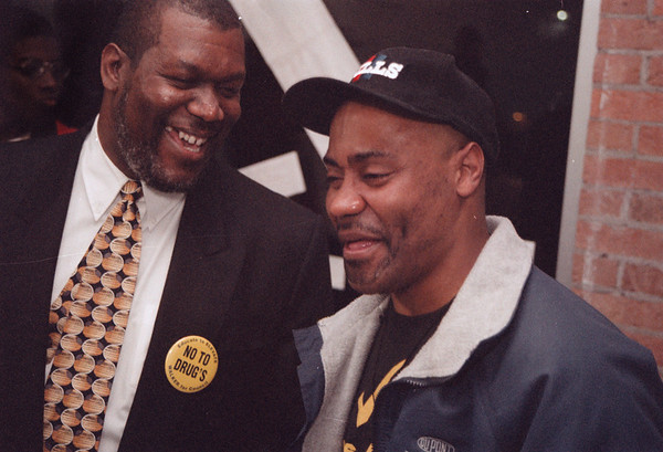 """98/11/3 Walker-Rachel Naber Photo-Charles Walker (left), new city councilman and an old friend Philip Vincent laugh as supports sing """"victory is mine""""."""