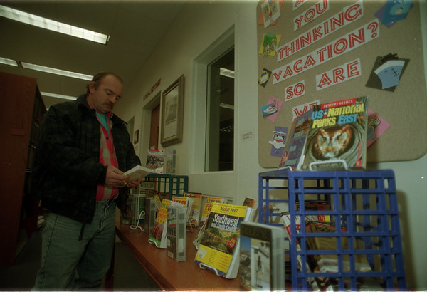 98/01/12 Vacations - James Neiss Photo - Enterprise Art - John Luss of Market Street Lockport was side tracked by a display on vacation destinations wile visiting the Lockport Library.