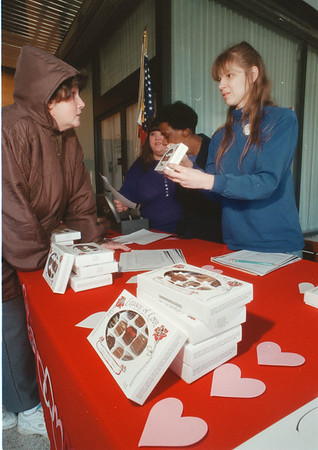 98/02/06 Legacy of Love - James Neiss Photo - Valerie LeMasters of 9th street buys a box of truffles from Wendy Washburn, a consumer from the  Opportunities Unlimited  Day Habilitation program, at the Niagara Office Building Lobby where they set up a booth.
