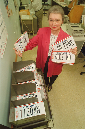 "6/2/97 Custom Plates - James Neiss Photo - Arlene M. Sweet, Deputy County Clerk, shows off custom ""County Clerk Plates"" and Custom License Plates at the DMV in Lockport."