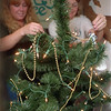 98/11/10 Memorial Tree-Rachel Naber Photo-Dawn Alello, local artisan (left) and Marion Fountain, hospice volunteer place ornaments on th memorial tree displayed in the front window of the United Way in Medina.
