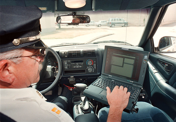 """97/08/07--LOCKPORT COPS & COMPUTERS--DAN CAPPELLAZZO PHOTO--LOCKPORT POLICE CAPTAIN JOHN CROSS ACCESSES INFORMATION FROM AN IN CAR LAPTOP USING THE """"ALECS"""" COMPUTER SOFTWEAR. THE SYSTEM IN TIED INTO ALBANY AND HELPS THE POLICE NETWORK INFO ON CRIMINALS AND THE DMV.<br /> <br /> 1A  TUESDAY"""