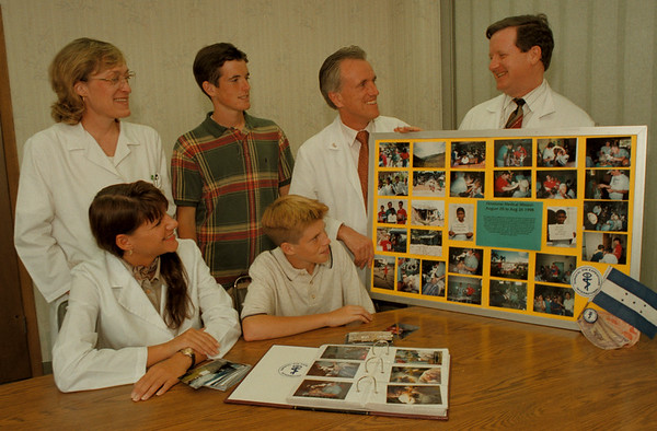 98/09/04 Fichte Eye Center *Dennis Stierer Photo -<br /> Looking at some photos and reminicing about their recent medical mission to Honduras are: sitting - Kathy Slater, Andrew Fichte;  (standing) Nancy Slater, Geoffrey Fichte, Dr. Claus Fichte, and Dr. William White.