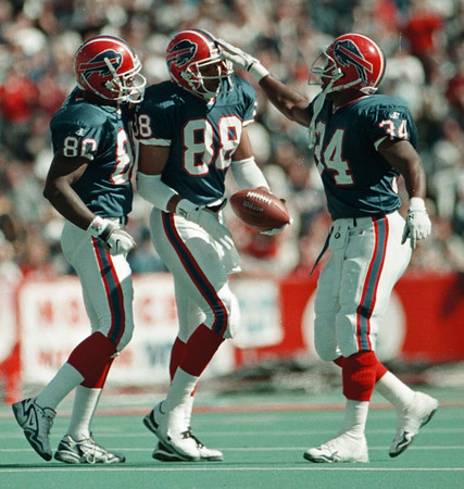 98/10/04 BILLS JUBO--DAN CAPPELLAZZO PHOT0--BILLS RECEIVER QUNN EARLY IS CONGRATULATED BY ERIC MOULDS, LEFT AND THURMAN THOMAS AFTER EARLY'S SECOND QUARTER TD RECPETION PUT THE BILLS UP 17-0.<br /> <br /> SP