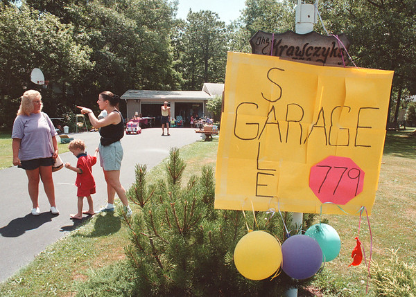 7/28/97--garage sale 1--Takaaki Iwabu photo-- The Krawczyks in Villege of Lewiston hangs the garage sale sign in their front yard to welcome the shoppers like Terri Costello, left. <br /> <br /> Sunday, Feature, color