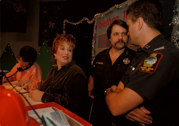 97/12/07-- Telethon --Takaaki Iwabu photo-- Niagara Falls fire fighters Dave Paonessa and Capt. Steve Kundl talk as Lori Dangelo, left, and Joelle Dangelo take telephone calls during the annual Telethon at Niagara Falls Convention and Civic Center. <br /> <br /> local, Monday, bw
