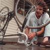97/09/17 fixing bike--Takaaki Iwabu photo-- Kevin Malone of Niagara Falls works on his bicycle in front of Community Mission building on Buffalo Ave. Wednesday. <br /> <br /> grapevine photo