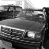 1/14/97--FOUND CAR--CAPPY PHOTO--DAVE SPURBACK OF PARKSIDE MOTORS, HYDE PK. BLVD. STANDS WITH A STOLEN CAR THAT TURNED UP IN THE GARAGES PARKING LOT.<br /> <br /> LOCLA