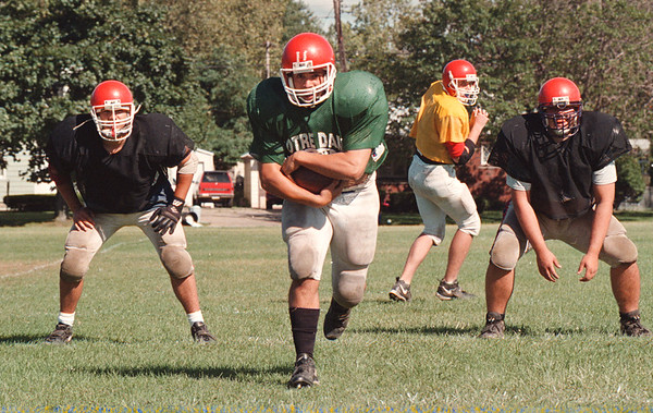 97/09/03--N.C. FOOTBALL--DAN CAPPELLAZZO PHOTO--NIAGARA CATHOLIC'S FAB FOUR POWERBACK LEN BEVILACQUA (CENTER) O-LINE VINCE PALLACI (LEFT) AND MATT VERMETTE HOLD THE LINE AS QB RYAN DOYDKA HANDS OFF.<br /> <br /> SP