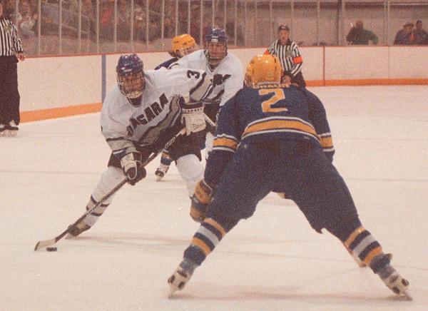 2/18/97 NU VS Canisius Hockey - James Neiss Photo - NU #3 Chris MacKenzie tries to drive the puck around Canisius #2 Jon Braun in the first period.<br /> <br /> Niagara University Hockey