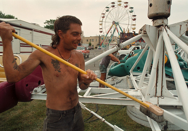 6/11/97-- preparing --Takaaki Iwabu photo-- Kodi Stephens of Amusements of Buffalo clean up one of many entertaining rides as he and other workers set up the annual St. John De LaSalle Carnival. <br /> <br /> local, Thursday