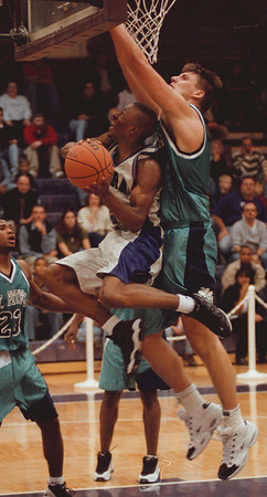 98/12/04 NU HOOPS--DAN CAPPELLAZZO PHOTO-- NU GUARD ALVIN YOUNG GOES UP FOR THE LAYUP AGAINST ST PETERS CENTER JAKE HOLMES IN FRIST HALF ACTION AT THE GALLAGHER CENTER.<br /> <br /> SP