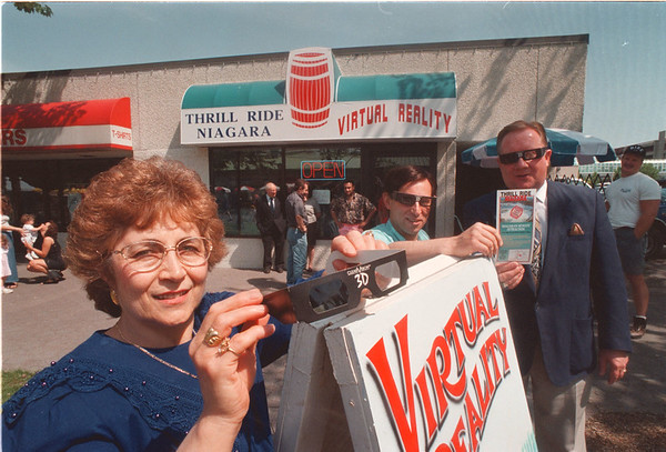 6/11/97 Thrill Ride Niagara - James Neiss Photo - Maria Roberto, President of Thrill Ride Niagara, shows a pair of the 3D glasses used for the new downtown attraction, as Patsy Roberto, Manager, shows mayor James Galie the brochure for the business.