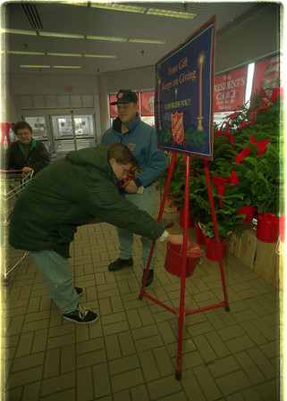 97/11/18 Salvation Army - James Neiss Photo - Jon Kleinhans of Lockport gives to the needy as Salvation Army Bell Ringer Mike Branch watches over the kettle at the Transit Rd. Tops in Lockport.