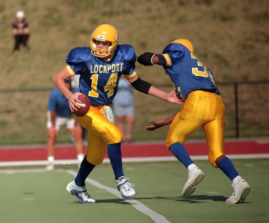 98/09/05 Lockport Football*Dennis Stierer Photo -<br /> Lockport's quarterback Scott Finn #14   fakes a handoff to running back  Kendrick Huston  #32. Lockport's home game was played at the old UB stadium in Amherst.