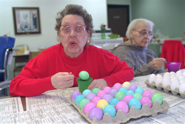 98/04/10 Coloring Eggs *Dennis Stierer photo - Coloring Easter Eggs can be fun for anyone at any age as Dorothy Walker shows off one of her green eggs while doing some of the more than 14 dozen eggs that were done on Friday at the Orchard Manor Nursing Home in Medina. Resident Angie Vanty is sitting to her right working on eggs too.