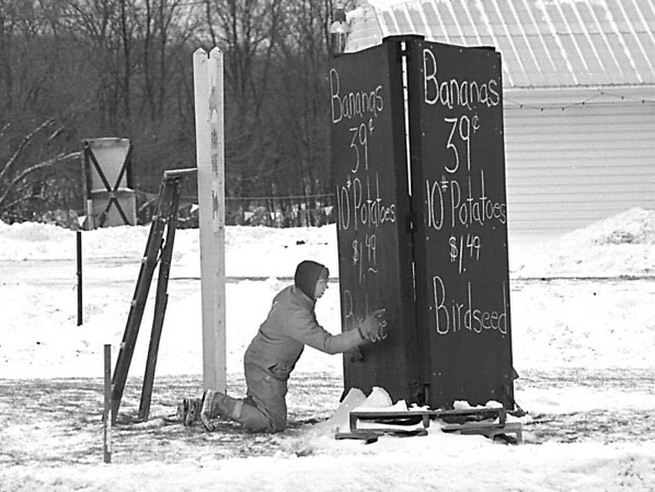 "1/13/97 Feed the Birds - James Neiss Photo - Ray Crawley, Manager of ""Goodmans Farm Market"" on Niagara Falls Blvd. updates a sign board reminding everyone to feed our feathered friends durring heavy snowfall."