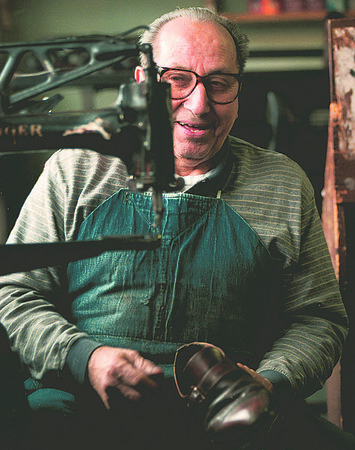 11/30/97--SHOEMAKER--DAN CAPPELLAZZO PHOTO--3RD STREET SHOEMAKER MARIO VOLPE HAS A LAUGH TALKING ABOUT HIS YEARS IN BUSINESS BEFORE SEWING THE BACK OF A SHOE.<br /> <br /> FEATURE SUNDAY