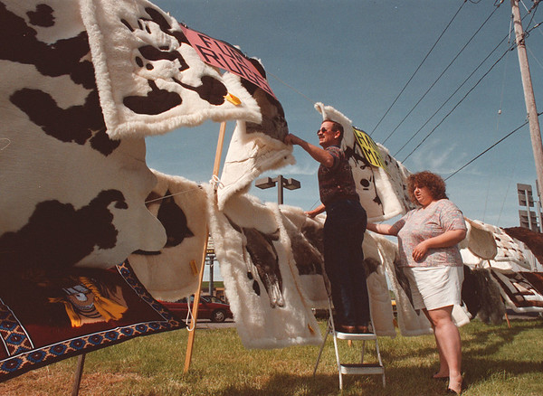 5/28/97 fur rugs --Takaaki Iwabu photo-- Earl Ward, left, shows fur rugs to Shannon Costa of Grand Island at Connecting Blvd. and Niagara Falls Blvd. Wednesday. Ward, from Jacksonville Florida, travels all over the States to sell imported fur rugs, cow hides and sheepskin. <br /> <br /> grapevine photo