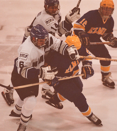 98/01/30--NU Hockey --Takaaki Iwabu photo-- Niagara University Peter DeSantis, front left, and Mike Isherwood give a hard check on Elmira players during Friday's game at NU. <br /> <br /> sports, color, Saturday