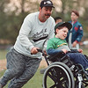 5/30/97-- H. baseball 1 --Takaaki Iwabu photo-- Michael Frail helps his son, Anthony, chasing a ball in the field as they play baseball game for handicapped children in Jayne Park Friday.<br /> <br /> Sunday 1A, color