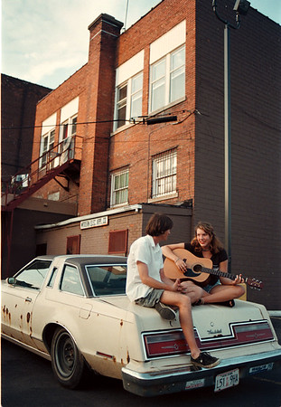 6/24/97-- guitar lesson--Takaaki Iwabu photo-- Amy Donaghue, right, 18, serenades her friend Bill Jenosheck of Youngstown as they were waiting their friends at the parking lot next to Main Street Tuesday.   <br /> <br /> grapevine photo