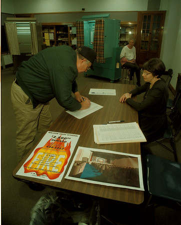 97/12/10  Wilson School Vote - James Neiss Photo - L-R - Joseph Kurtz of Wilson signs up to vote with the help of Carole Schnoor, School Secretary. In back ground is Election Inspector Margaret Siener. The hot topic was the approval of funds to redo the school auditorium that burned at the hands of an arson.